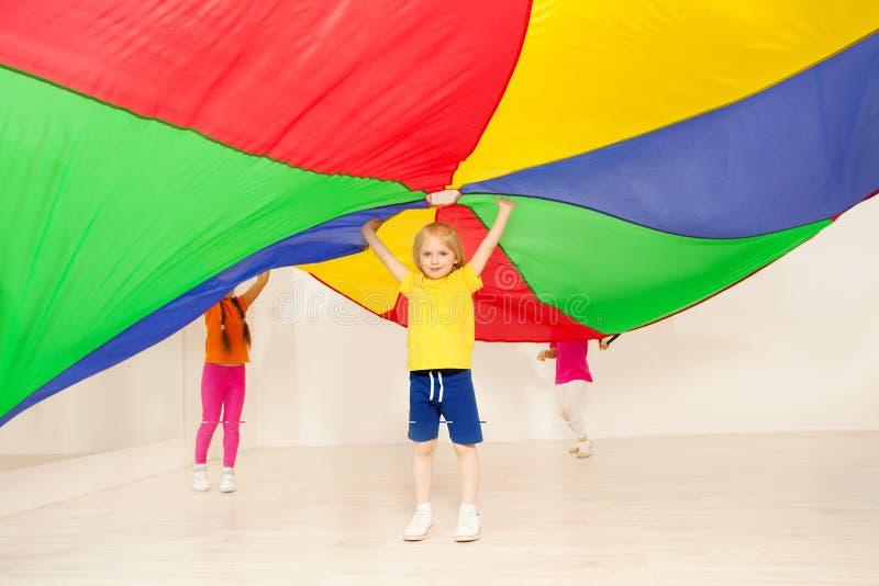 Śliczna chłopiec pozycja pod dużym namiotem robić spadochron fotografia stock