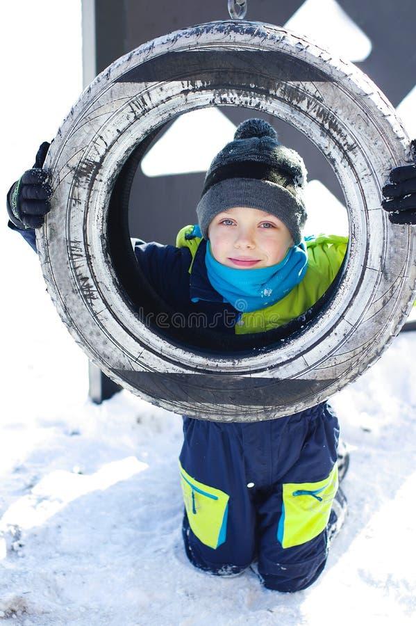 Śliczna chłopiec przejażdżka na huśtawce w zimie szczęśliwi dzieci ma zabawę, bawić się przy zima spacerem outdoors zdjęcia royalty free