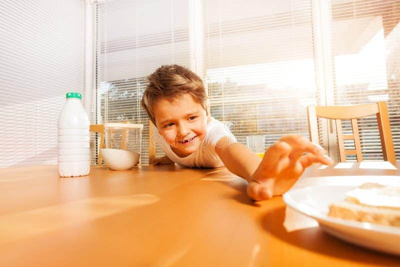 Śliczna chłopiec robi długiej ręce dla talerza z kanapką obraz royalty free