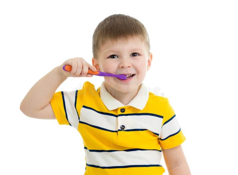 Śliczna chłopiec szczotkuje zęby, odizolowywających na bielu fotografia royalty free