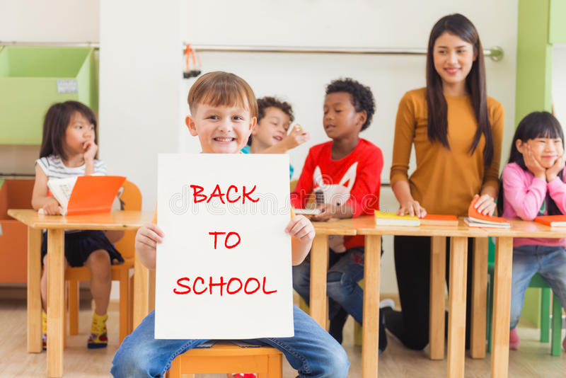 Śliczna chłopiec trzyma z powrotem szkoła plakat z szczęśliwą twarzą w dzieciniec sala lekcyjnej, dzieciniec edukaci pojęcie zdjęcie royalty free