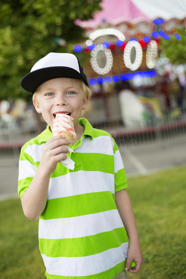 Śliczna chłopiec uśmiecha się jego lody i liże przy plenerowym karnawałem zdjęcie stock