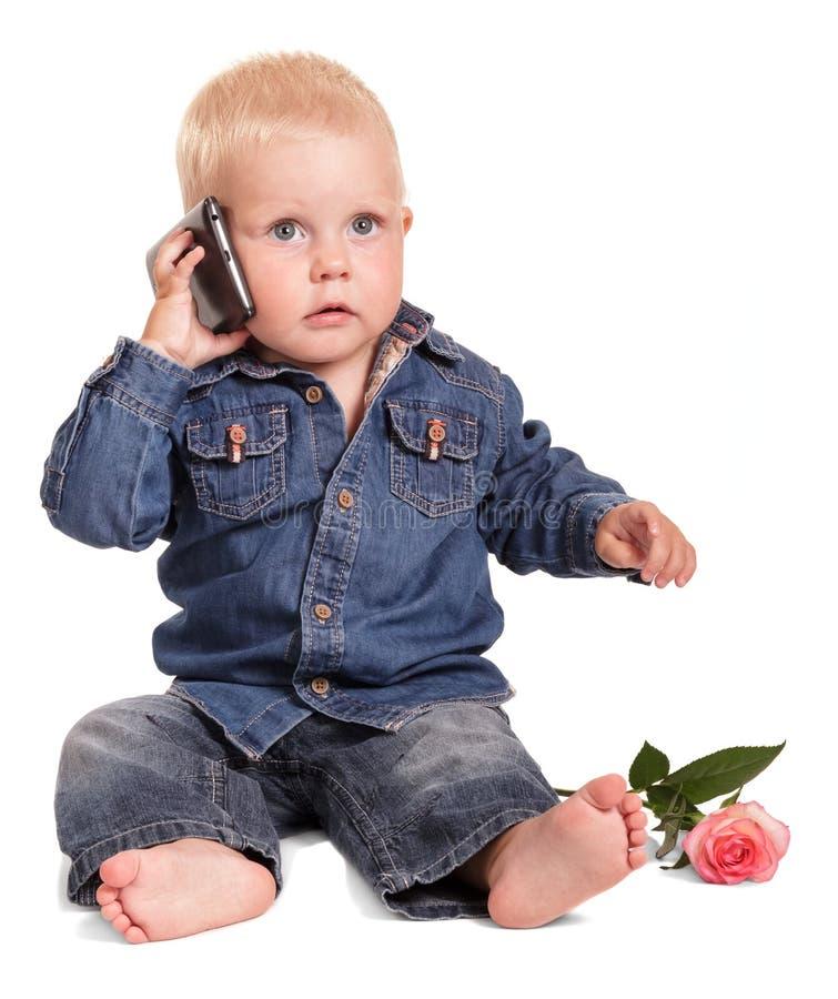 Śliczna chłopiec w błękitnej koszula i cajgach siedzi, trzyma wiszącą ozdobę ph zdjęcie royalty free