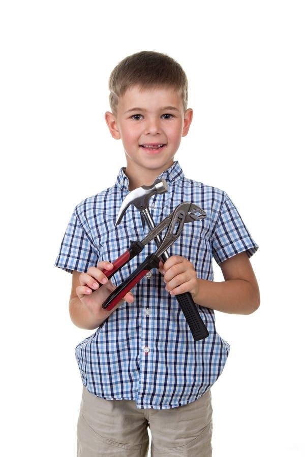 Śliczna chłopiec w błękitnej w kratkę koszula, trzyma budynków instrumenty, odizolowywających na białym tle obraz royalty free