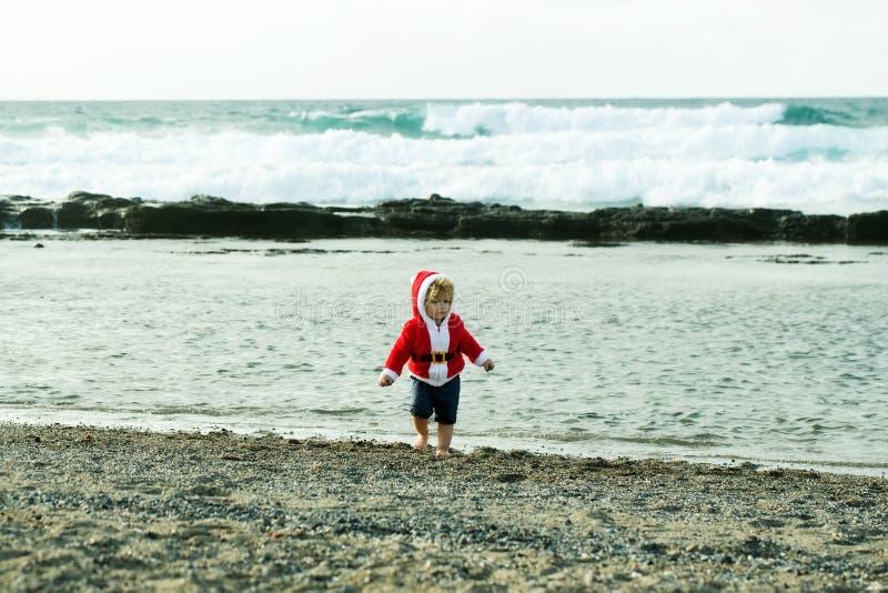 Śliczna chłopiec w czerwonym Santa żakiecie na otoczak plaży obraz royalty free