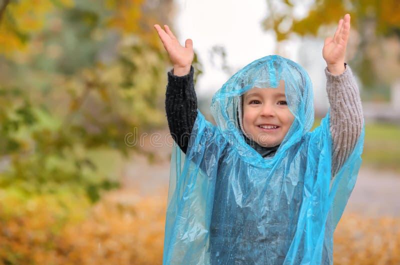 Śliczna chłopiec w deszczowu ma zabawę w jesień parku zdjęcia royalty free