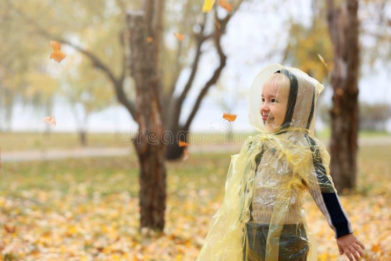 Śliczna chłopiec w deszczowu ma zabawę w jesień parku obraz stock