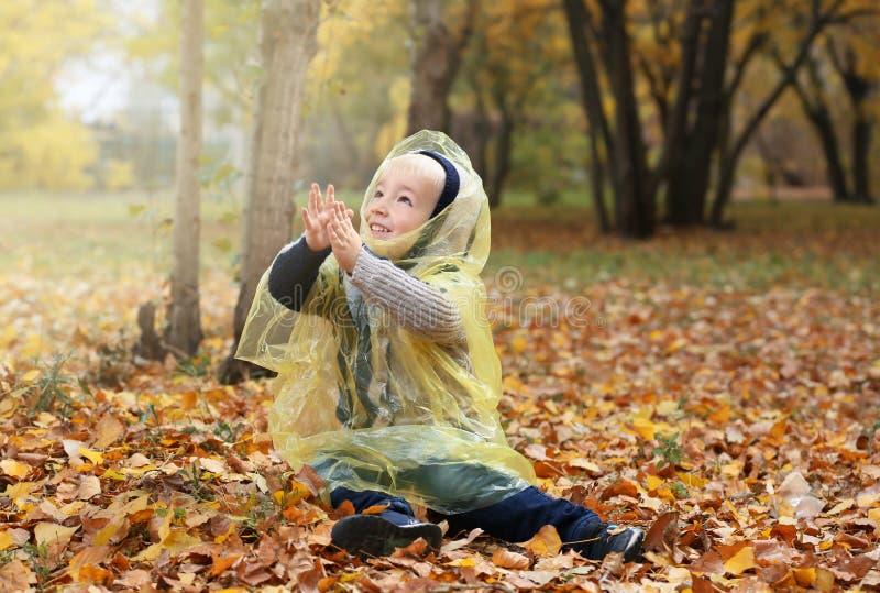 Śliczna chłopiec w deszczowu ma zabawę w jesień parku obrazy royalty free