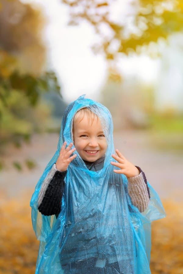 Śliczna chłopiec w deszczowu ma zabawę w jesień parku fotografia royalty free
