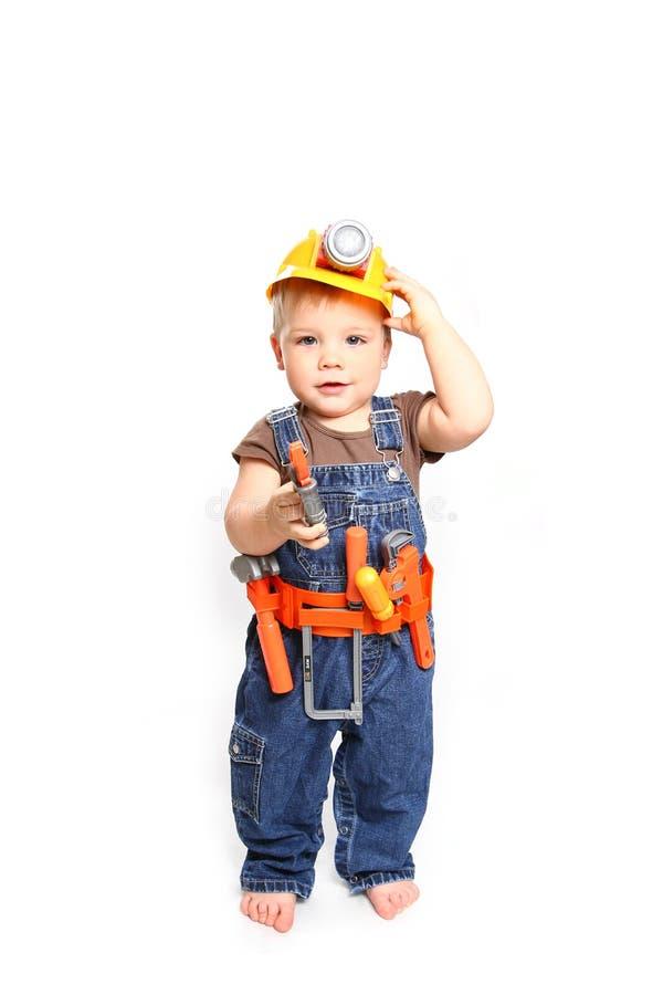 Śliczna chłopiec w pomarańczowym hełmie i narzędzia na białym backgro obrazy stock
