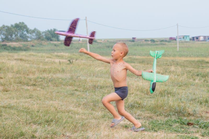 Śliczna chłopiec w skrótach biega przez pole i wszczyna zabawkarskiego samolot fotografia royalty free
