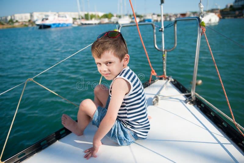 Śliczna chłopiec w skrótach i pasiastej koszulce siedzi na pokładzie jachtu w porcie morskim obraz royalty free