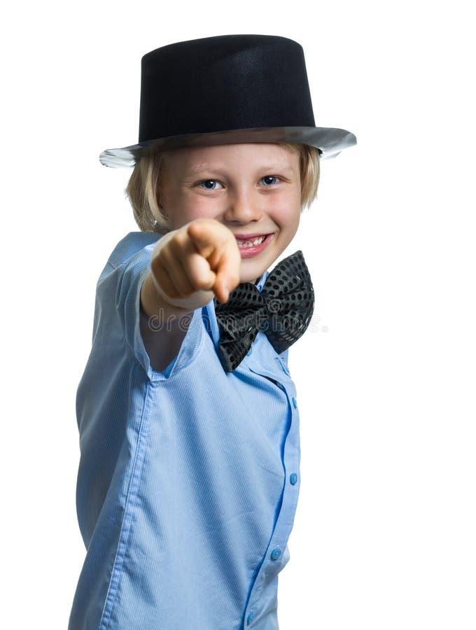 Śliczna chłopiec wskazuje z odgórnym kapeluszem i łęku krawatem kamera. zdjęcie stock