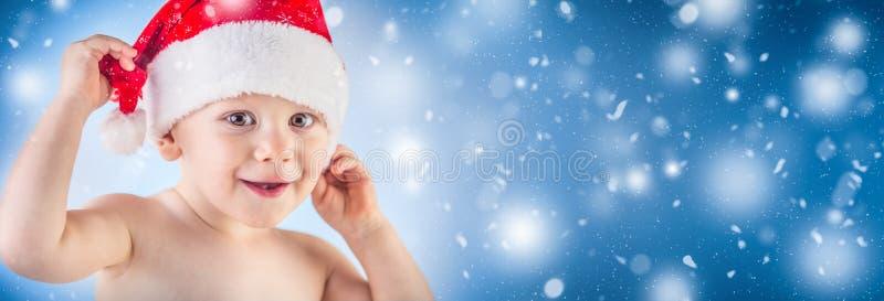 Śliczna chłopiec z boże narodzenie nakrętką w abstrakcjonistycznych śnieżnych panoramicznych półdupkach obrazy royalty free