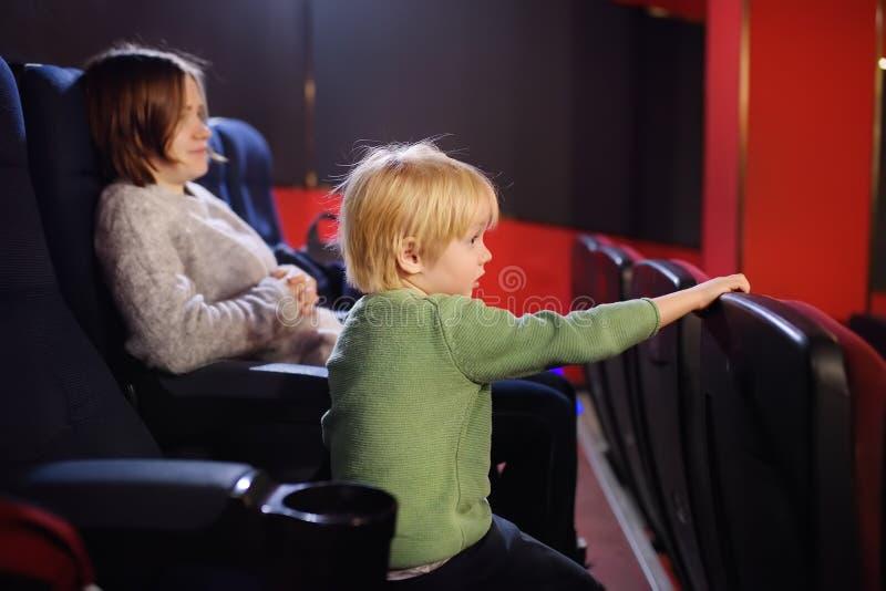 Śliczna chłopiec z jego macierzystym dopatrywanie kreskówki filmem w kinie obraz stock