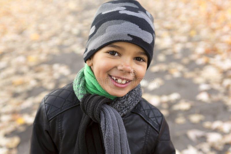 Śliczna chłopiec z jesień liśćmi w parku fotografia royalty free