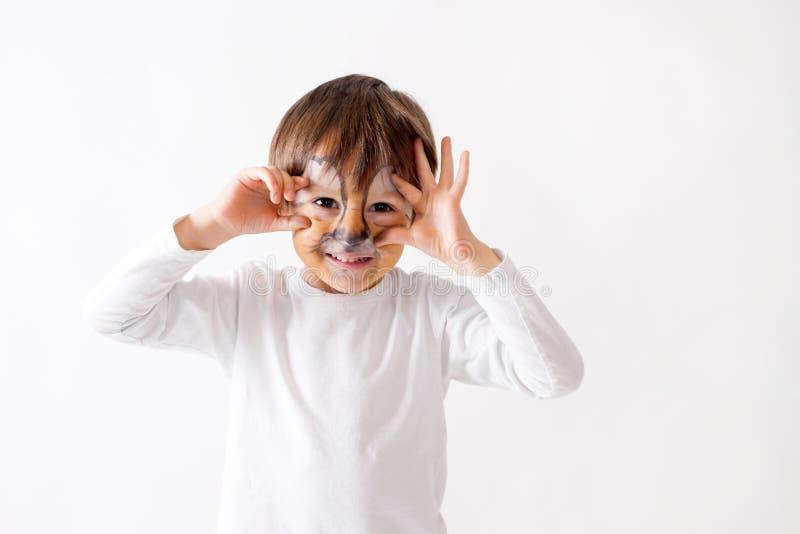 Śliczna chłopiec z malującą twarzą jako lew, mieć zabawę fotografia royalty free