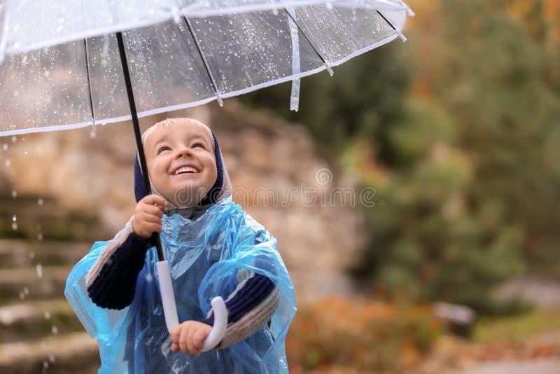 Śliczna chłopiec z przejrzystym parasolem pod deszczem outdoors zdjęcie stock