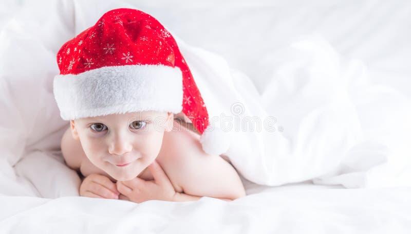 Śliczna chłopiec z Santa kapeluszem na łóżku pod białym duvet zdjęcia stock