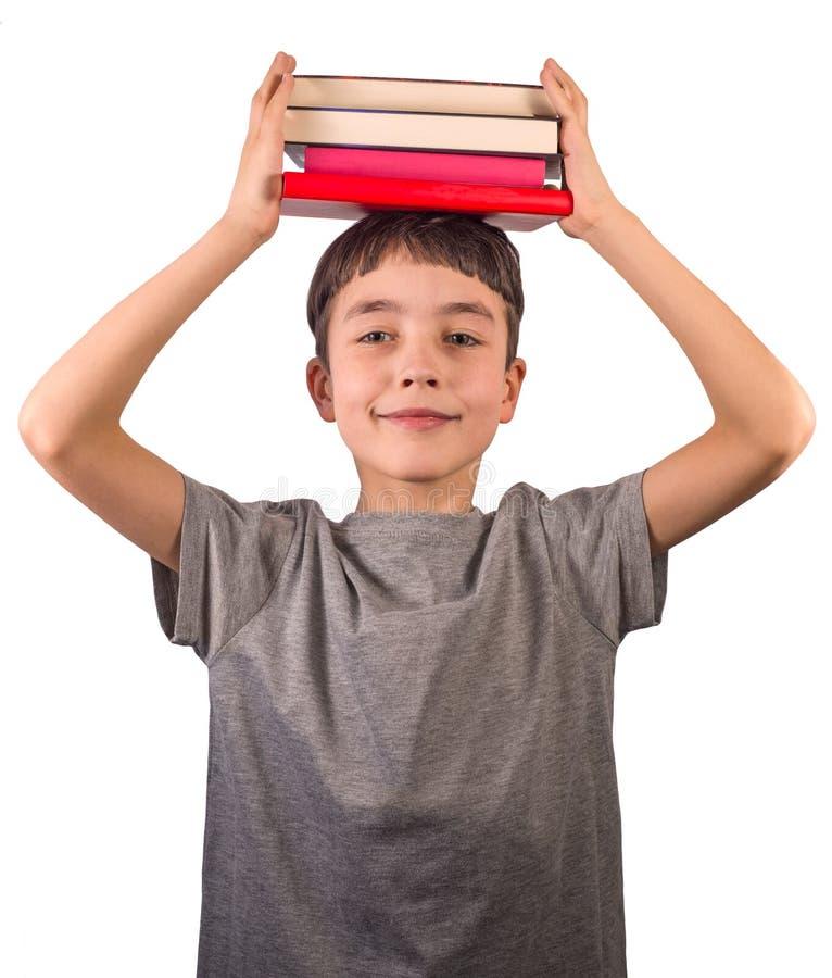 Śliczna chłopiec z stertą książki na jego głowa ono uśmiecha się na białym tle obrazy royalty free