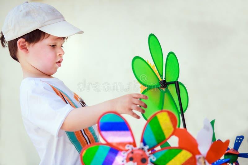 Śliczna chłopiec z wiatraczkiem bawi się outdoors zdjęcia royalty free