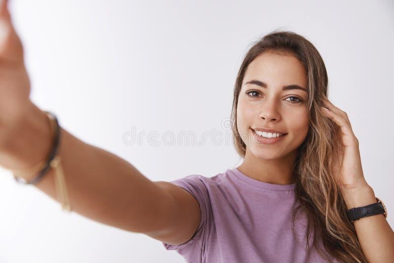 Śliczna charyzmatyczna szczęśliwa młoda caucasian dziewczyna sprawdza ostrzyżenie wzruszającego włosy przedłużyć rękę w kierunku  zdjęcie stock