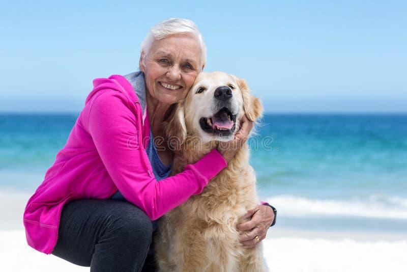 Śliczna dojrzała kobieta migdali jej psa obraz stock
