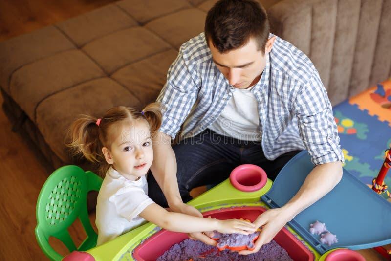 Śliczna dzieciak dziewczyna, ojciec bawić się z kinetycznym piaskiem w domu i obrazy stock