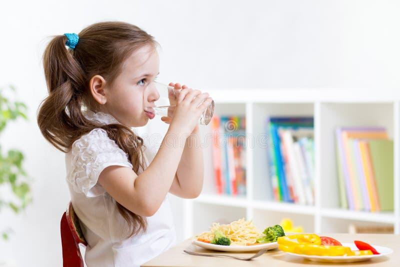Śliczna dzieciak dziewczyny woda pitna w domu zdjęcie royalty free