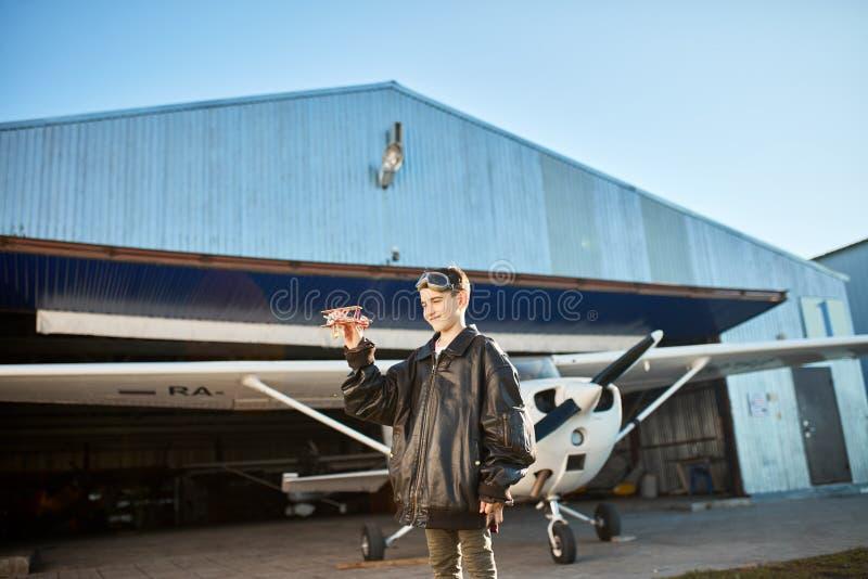 Śliczna dzieciak pozycja bawić się z wzorcowym samolotem, jest ubranym ampułę pilotuje kurtkę zdjęcie stock