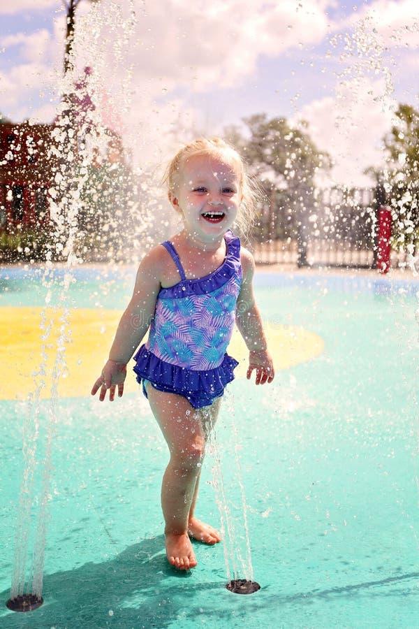 Śliczna dziecko berbecia dziewczyna Bawić się Outside w wodzie przy pluśnięcie parkiem fotografia royalty free