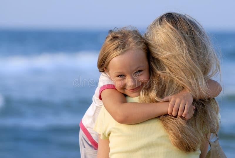 Śliczna dziewczyna ściska jej mamy na plaży zdjęcie stock