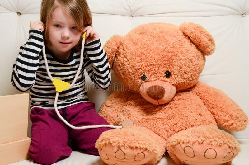 Śliczna dziewczyna bawić się lekarkę z mokiet zabawki niedźwiedziem zdjęcia royalty free