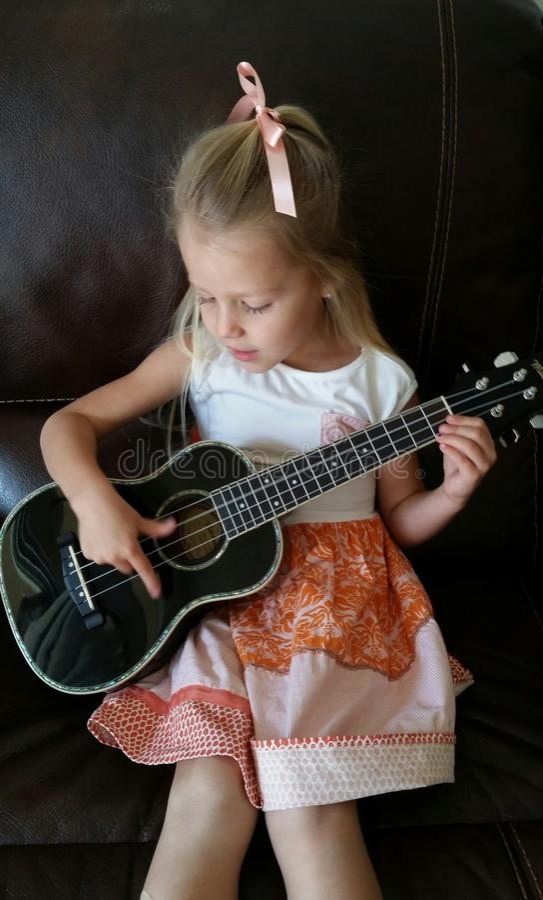 Śliczna dziewczyna bawić się ukulele zdjęcie stock