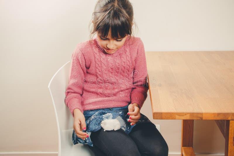 Śliczna dziewczyna bawić się z jej chomikiem obraz stock