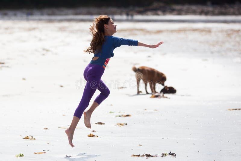 Śliczna dziewczyna biega szczęśliwego przy plażą obraz royalty free