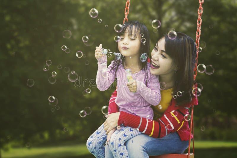 Śliczna dziewczyna i matka dmucha mydlanych bąble zdjęcia stock