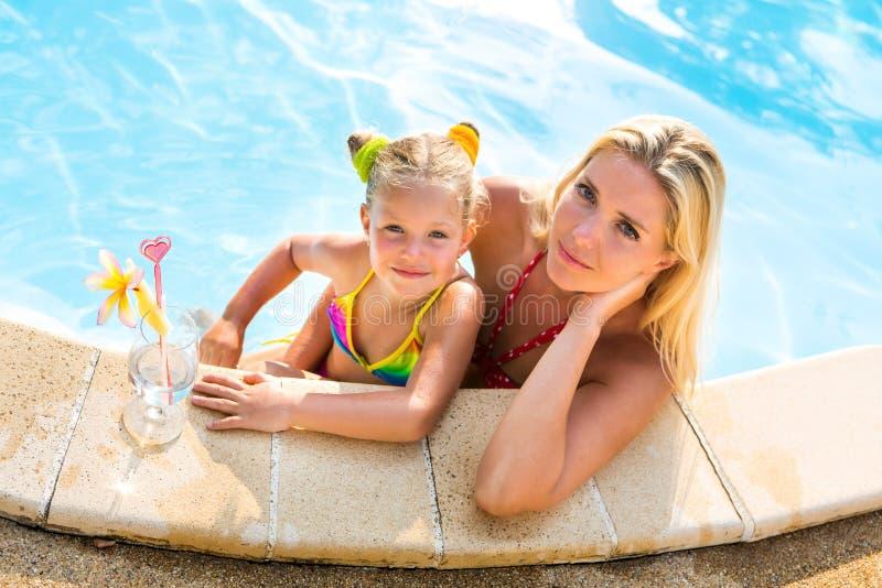 Śliczna dziewczyna i piękna matka przy basenem fotografia stock