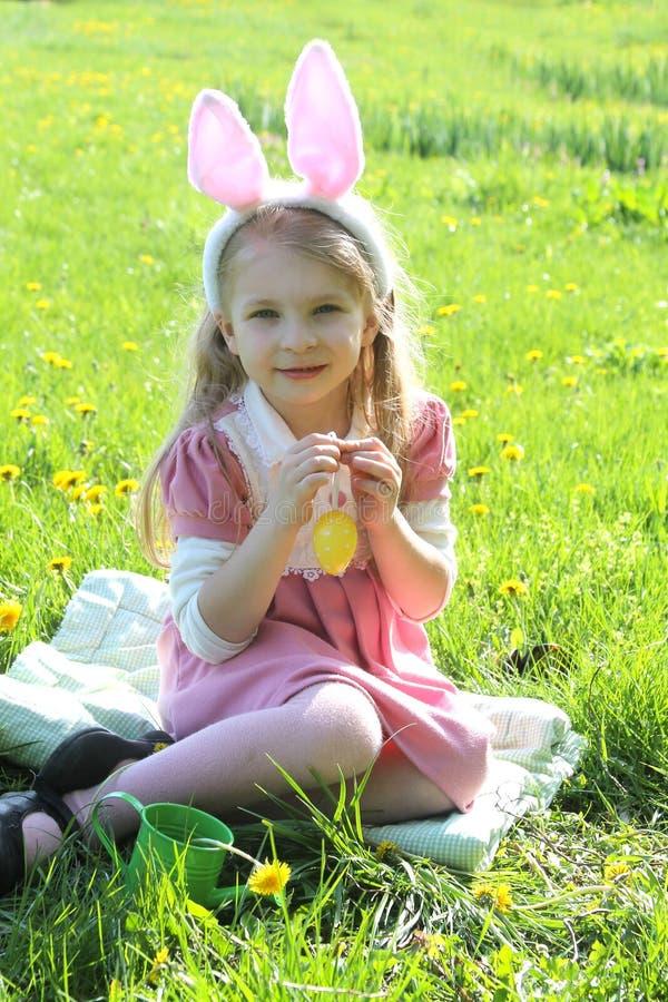 Śliczna dziewczyna jest ubranym ucho przy wiosny zieloną trawą z królikiem zdjęcie stock