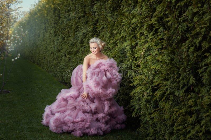 Śliczna dziewczyna muska jego ręk menchii suknię fotografia royalty free