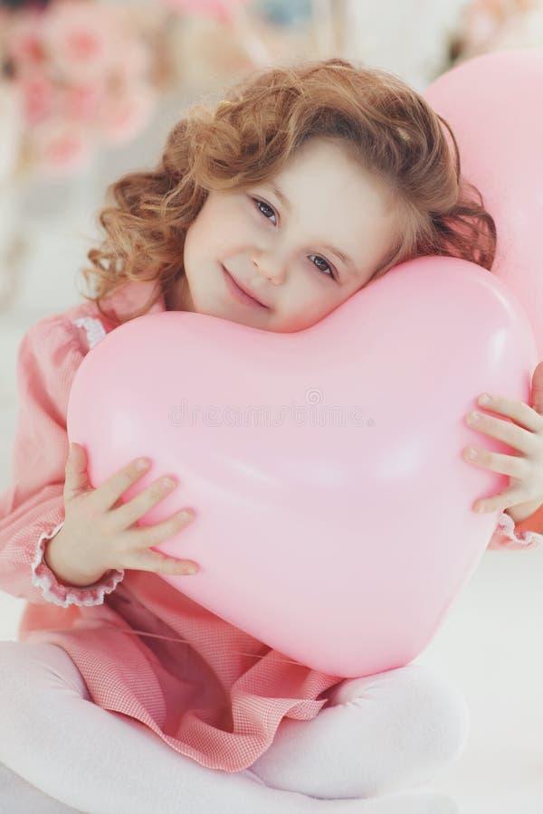 Śliczna dziewczyna na białej podłodze w studiu z wiązką różowi balony obrazy stock