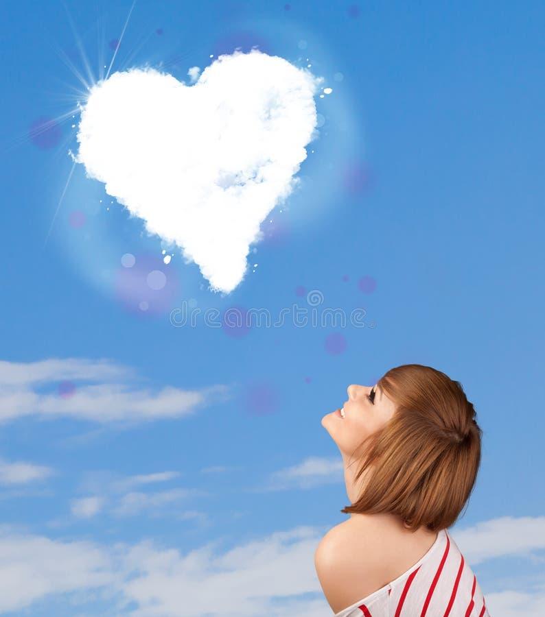 Śliczna dziewczyna patrzeje białą serce chmurę na niebieskim niebie fotografia stock