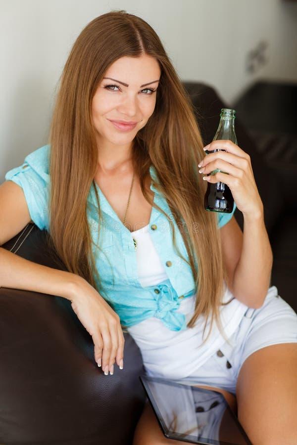 Śliczna dziewczyna pije koka-koli od butelki, siedzi na leżance obrazy stock