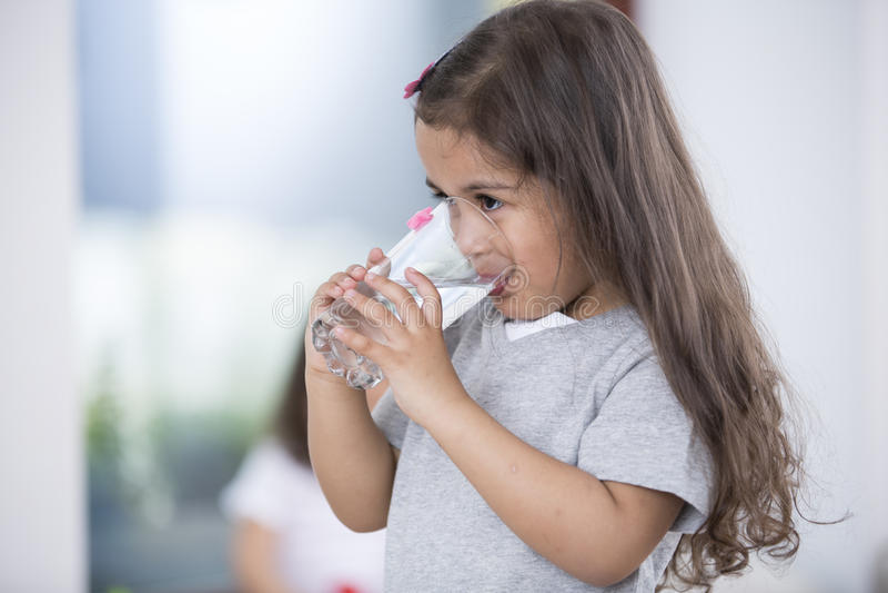 Śliczna dziewczyna pije szkło woda w domu obraz royalty free