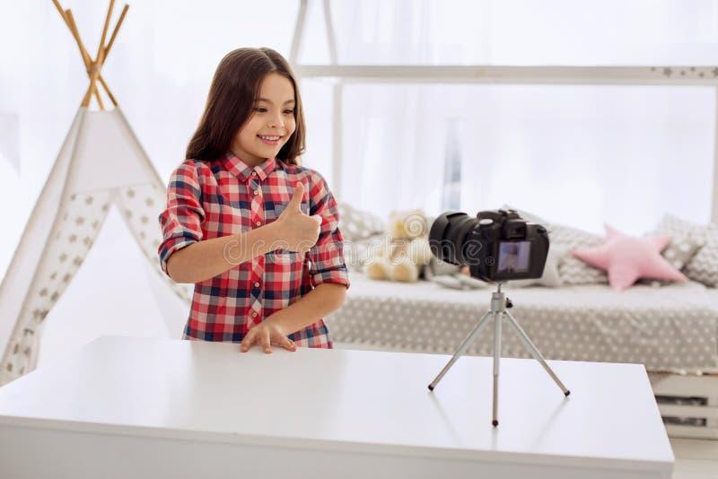 Śliczna dziewczyna pokazuje aprobaty podczas gdy nagrywający vlog zdjęcia stock