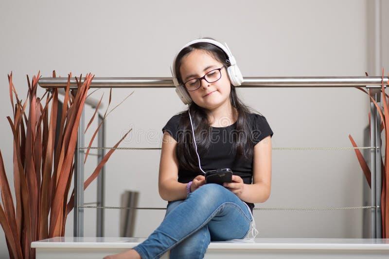 Śliczna dziewczyna słucha muzyka z szkłami zdjęcie royalty free