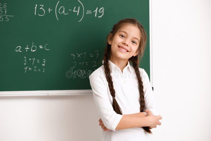Śliczna dziewczyna stoi blisko chalkboard w sali lekcyjnej obrazy stock