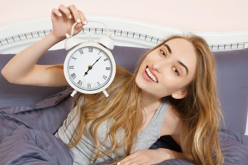 Śliczna dziewczyna trzyma zegar i kłama w łóżkowej sypialni Emocjonalny piękny kobiety lying on the beach w łóżku na jej dniu wol obrazy stock
