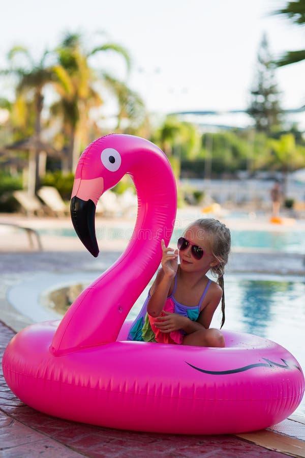 Śliczna dziewczyna w flaminga okręgu w basenie m?odzi doro?li wakacje fotografia stock