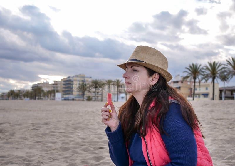 Śliczna dziewczyna w kapeluszu je arbuza podczas gdy siedzący na plaży zdjęcie stock